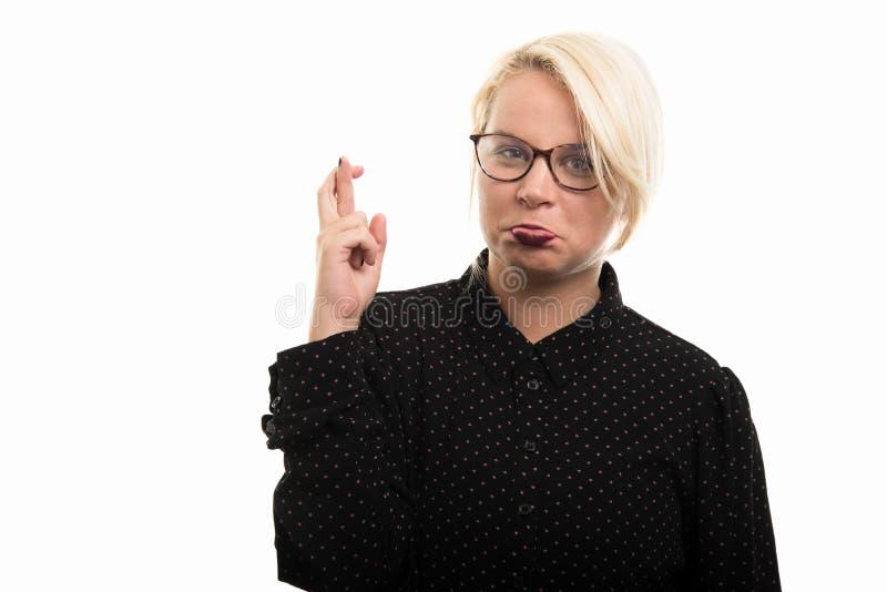 Blonde vrouwelijke leraar die glazen dragen die dwarsvingergestu tonen royalty-vrije stock foto's