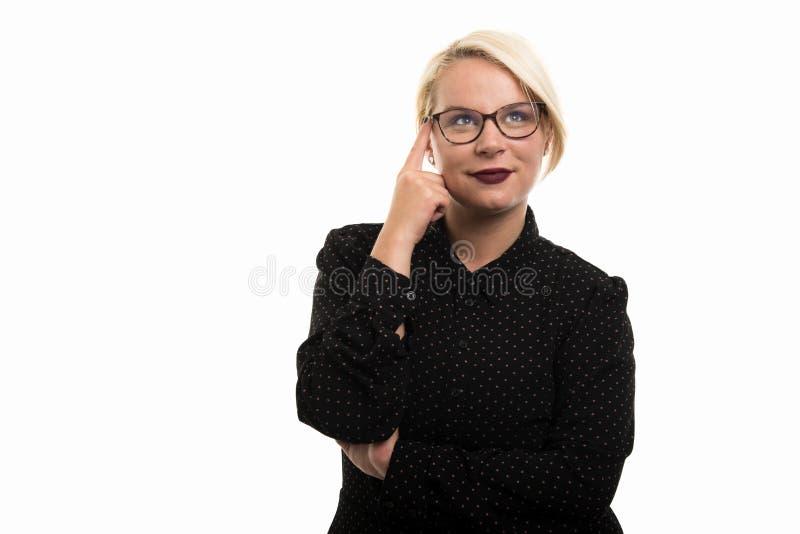 Blonde vrouwelijke leraar die glazen dragen die het denken gebaar tonen stock afbeelding
