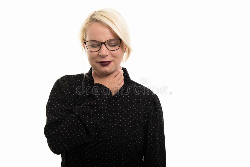 Blonde vrouwelijke leraar die glazen dragen die keelpijn tonen gestur stock fotografie