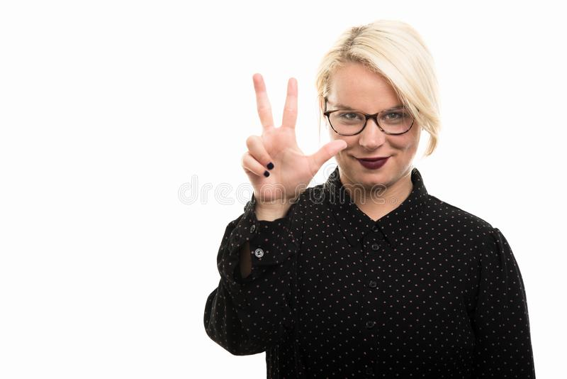 Blonde vrouwelijke leraar die glazen dragen die nummer drie tonen met royalty-vrije stock foto