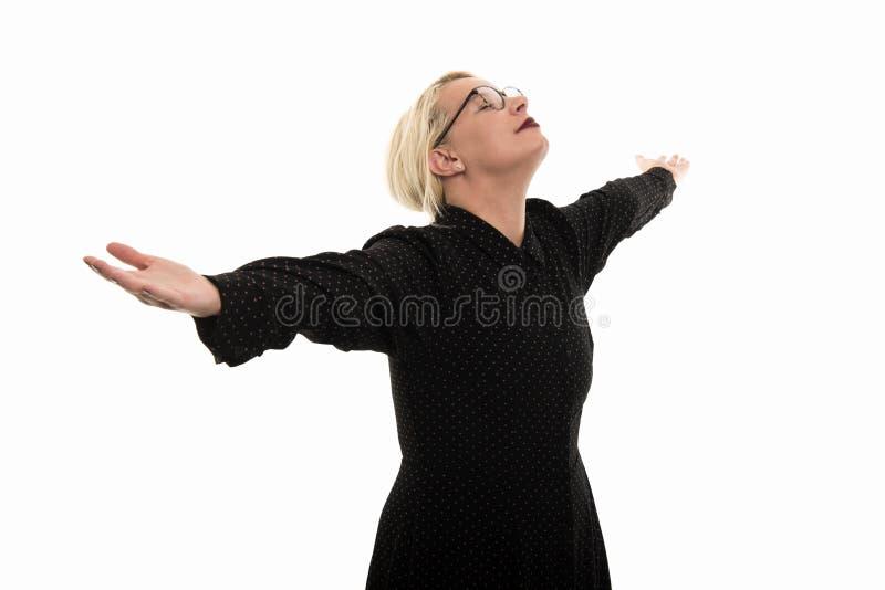 Blonde vrouwelijke leraar die glazen dragen die omhoog met open wapens kijken royalty-vrije stock afbeelding