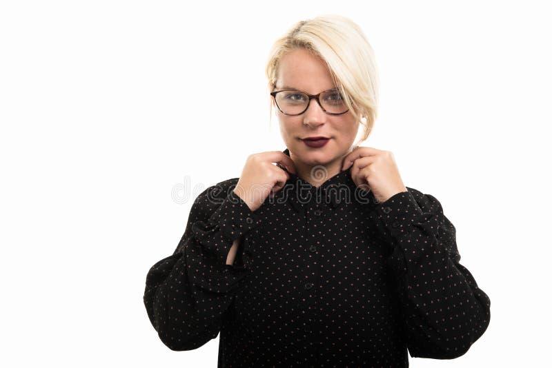 Blonde vrouwelijke leraar die glazen dragen die overhemdskraag schikken royalty-vrije stock fotografie