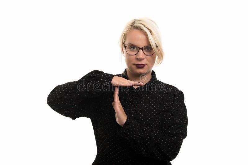 Blonde vrouwelijke leraar die glazen dragen die tijd uit gebaar tonen stock afbeelding