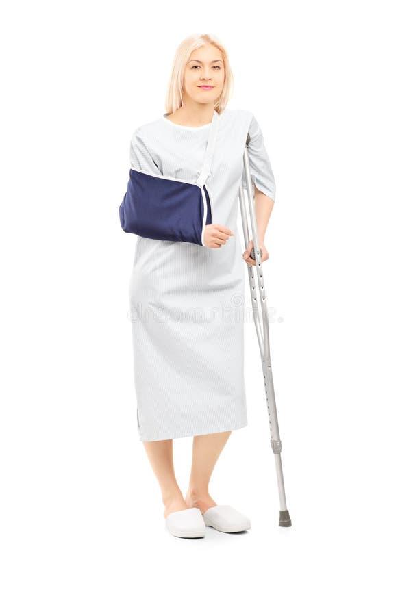 Blonde vrouwelijke patiënt in toga met gebroken wapen en steunpilaar royalty-vrije stock fotografie