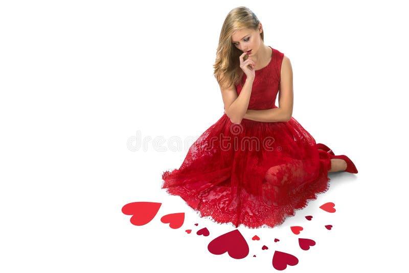 Blonde vrouwen rode harten die geïsoleerd Valentine zitten stock afbeeldingen