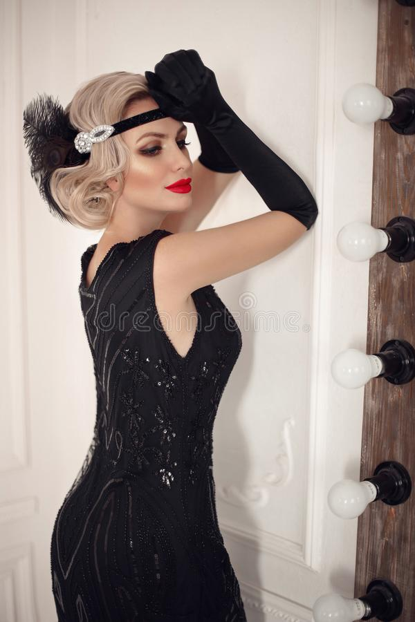 Blonde wavy hairstyle. Elegant woman portrait in retro style. Beautiful girl wears in vintage black dress and gloves. Hollywood royalty free stock image