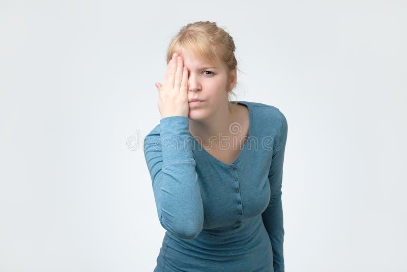 Blonde weibliche schauende Kamera, ihr Auge mit einer Hand bedeckend stockbilder