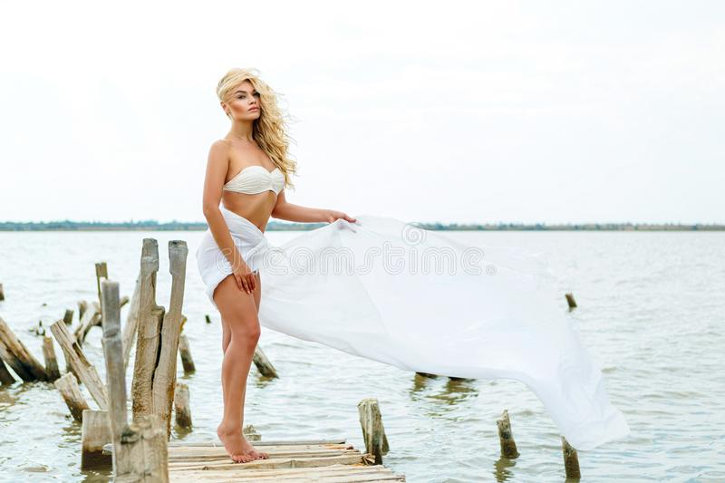Blonde in a white bathing suit, standing on the background of the lake in the wind, rest and relaxation stock photos