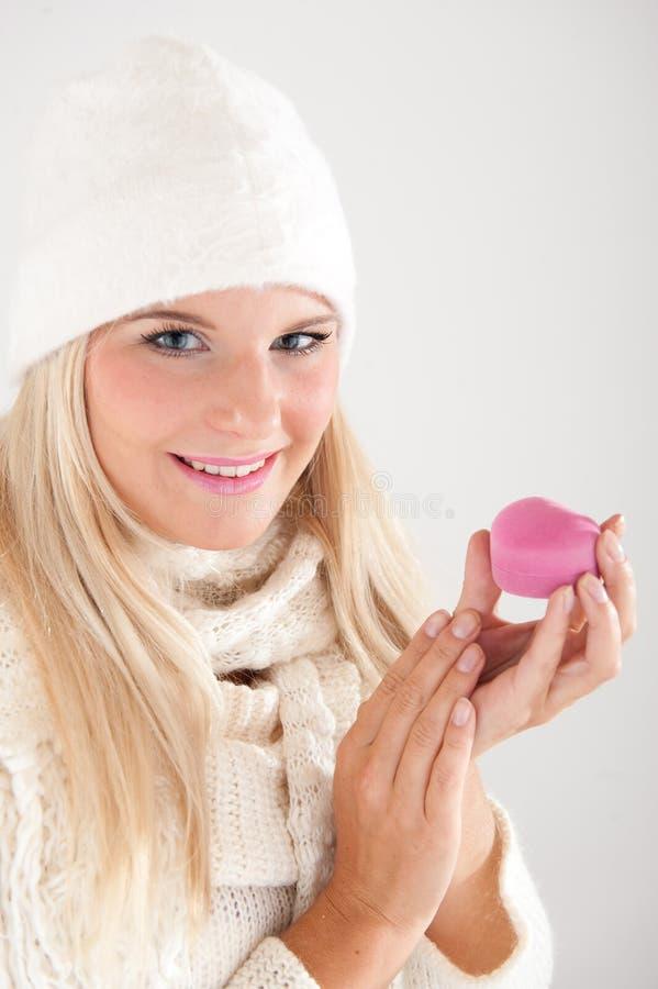 Blonde Winterfrau in einem Hut, der ein Geschenk hat stockfotografie