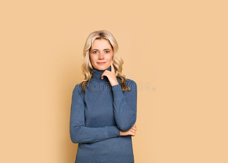 Blonde woman adult attractive beautiful calm  portrait  face, cauasian and scandinavian girl in blue sweater on yellow background. Autumn theme, copy space royalty free stock photos