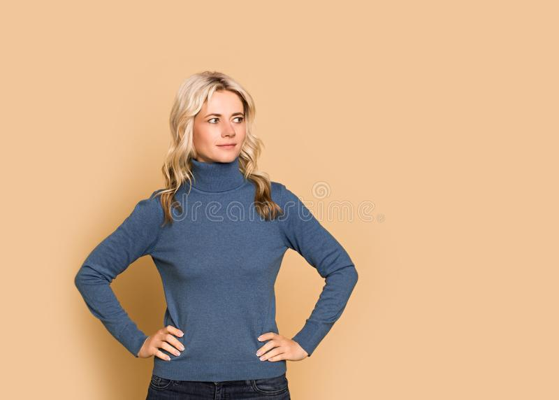 Blonde woman adult attractive beautiful calm  portrait  face, cauasian and scandinavian girl in blue sweater on yellow background. Autumn theme, copy space royalty free stock photo