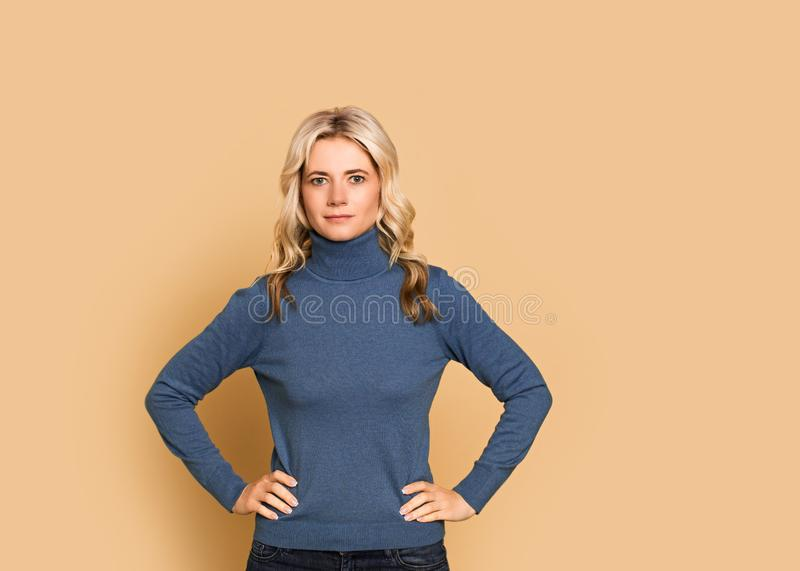 Blonde woman adult attractive beautiful calm  portrait  face, cauasian and scandinavian girl in blue sweater on yellow background. Autumn theme, copy space stock photos