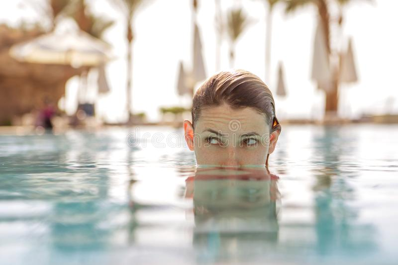 Blonde woman with almost all her head in water on swimming pool. In tropical resort. Eyes looking sideways, girl deciding something strangely. Copy space royalty free stock photo