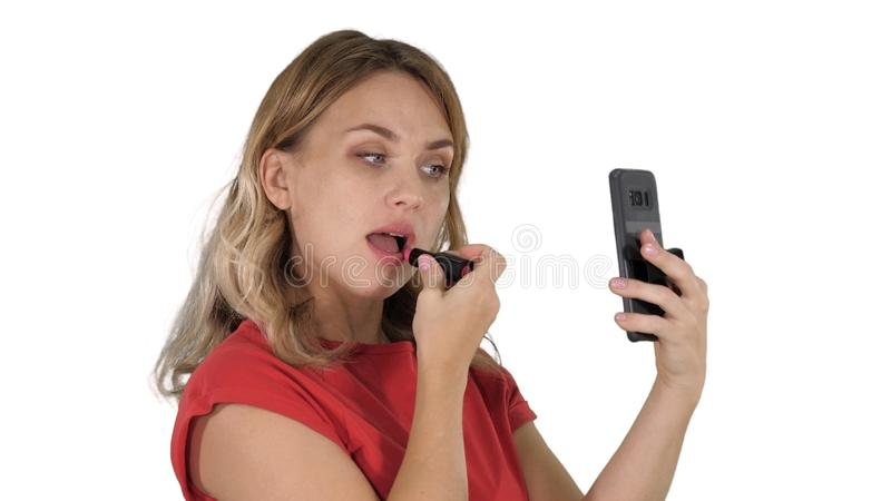 Blonde woman applying lipstick looking in the phone on white background. stock image