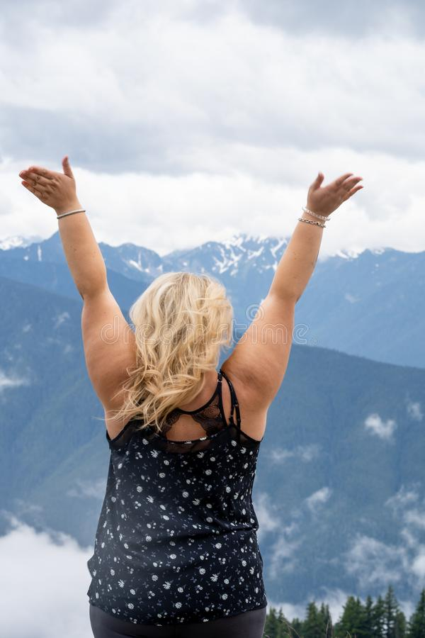 Blonde woman with back facing the camera has arms raised at Hurricane Ridge in Olympic National Park royalty free stock image