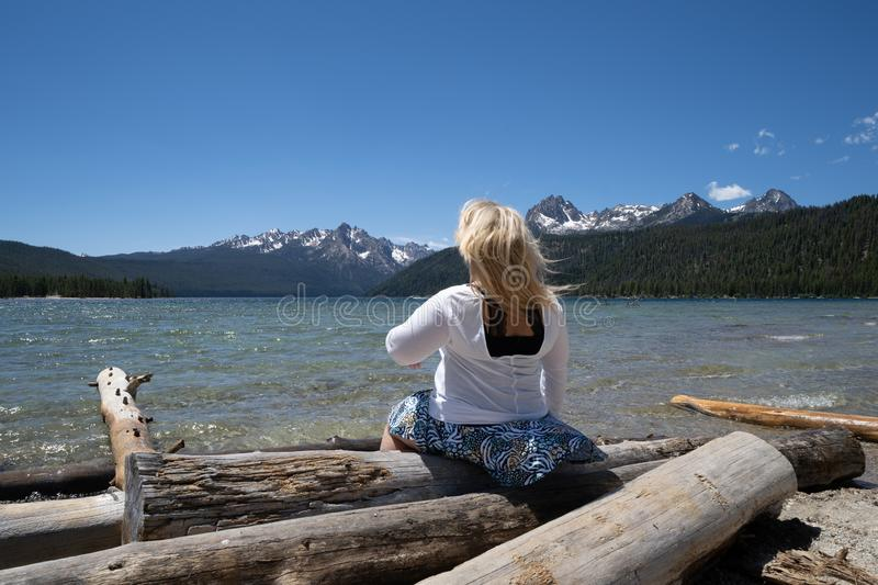 Blonde woman with back facing camera looks out to the Sawtooth Mountains while sitting on logs at Redfish Lake. Wind blows her stock photography