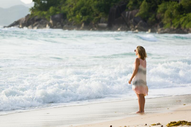 Blonde woman in beach dress enjoys the tropical sunset, looking at the sea, in Seychelles. royalty free stock photography