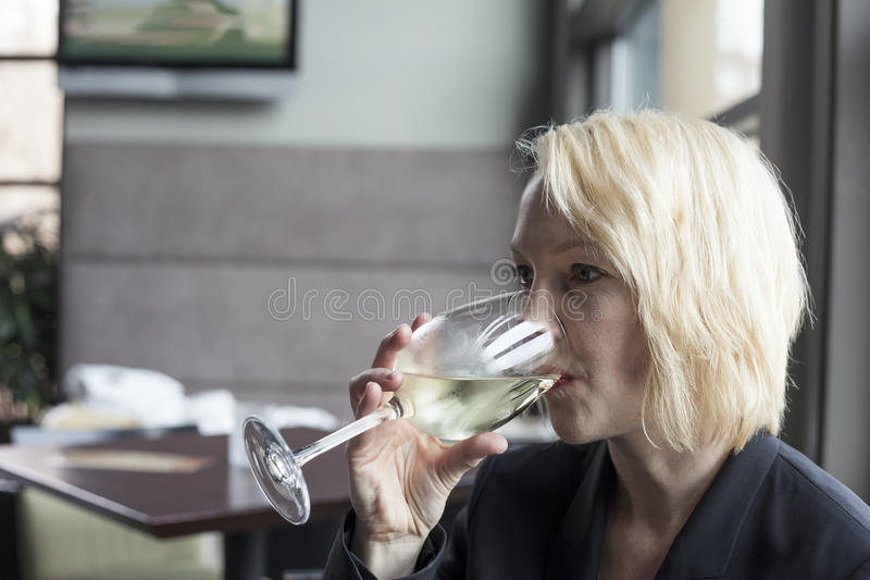 Blonde Woman with Beautiful Blue Eyes Drinking Glass of White Wi royalty free stock photo