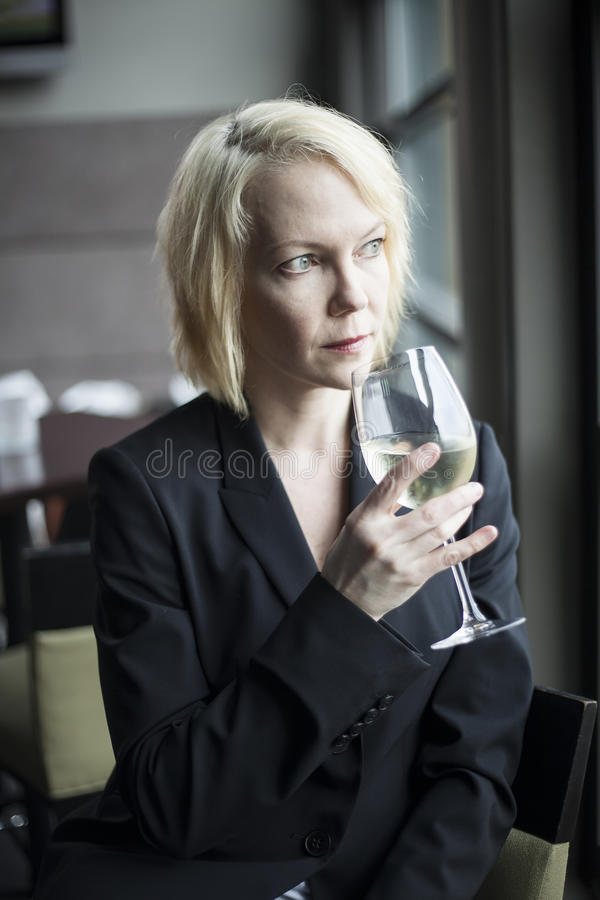 Blonde Woman with Beautiful Blue Eyes Drinking Glass of White Wi stock images