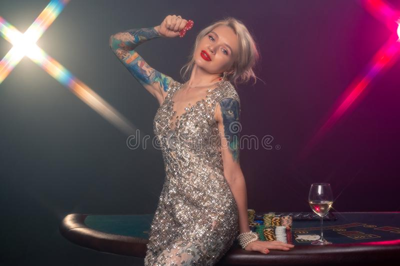 Blonde woman with a beautiful hairstyle and perfect make-up is posing with red gambling chips in her hands. Casino stock photos