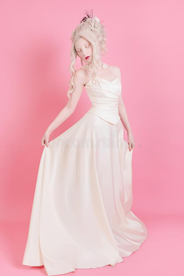 Blonde woman with beautiful luxurious rococo hair style. A blond woman with a beautiful luxurious rococo hair style in a white dress on a pink background royalty free stock photo