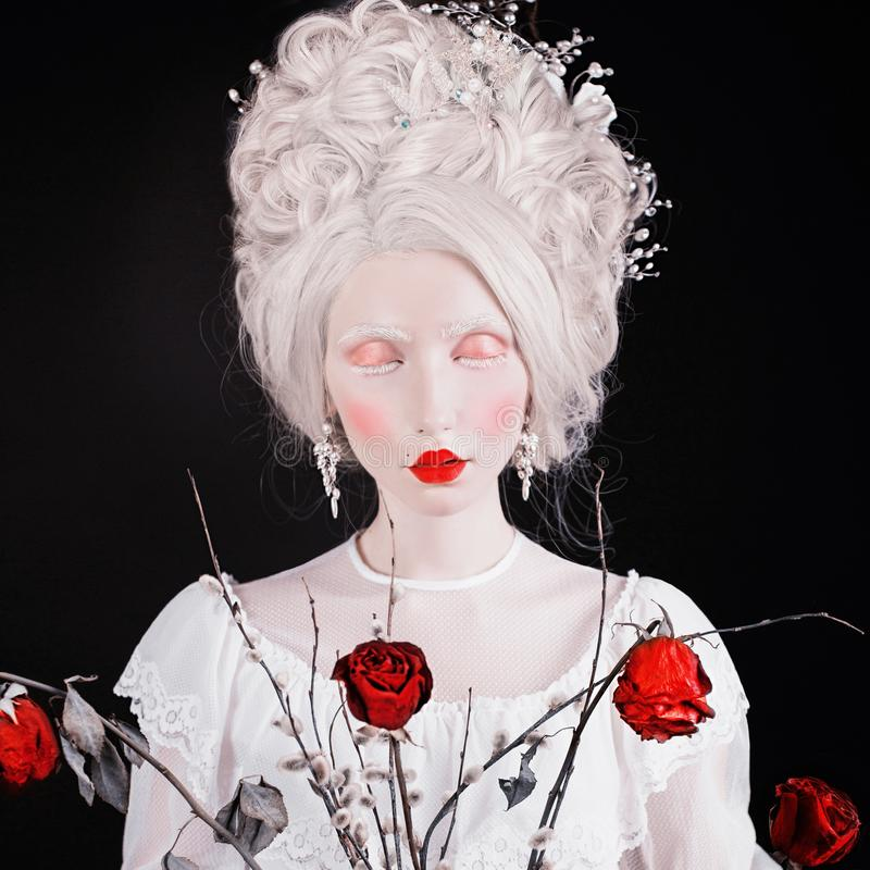 Blonde woman with beautiful luxurious rococo hairstyle in white dress with rose flowers. Albino model. Young renaissance blonde stock photography