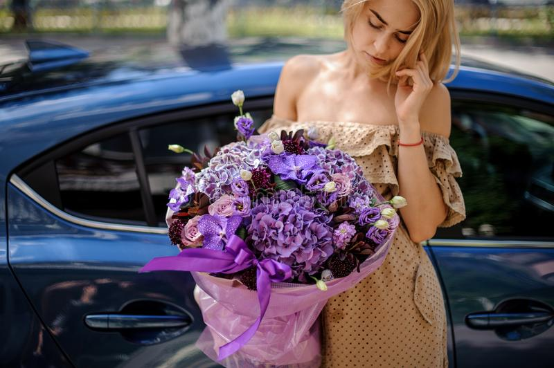 Blonde woman in beige dress holding a big bouquet of flowers in stock photos