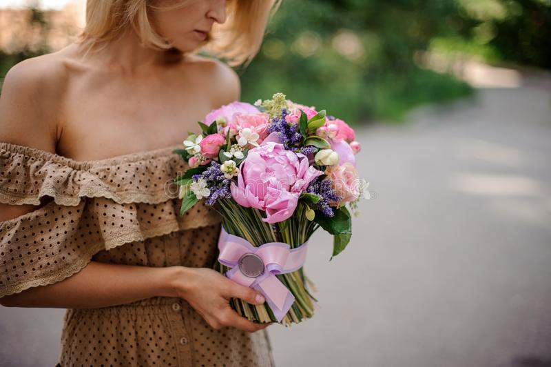 Blonde woman in beige dress holding a tender pink bouquet of flo royalty free stock photo