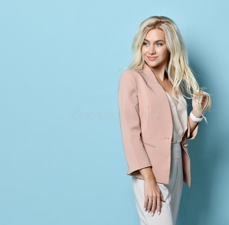 Woman in beige jacket, white overall. Smiling, touching her hair, standing sideways against blue studio background. Close-up royalty free stock images