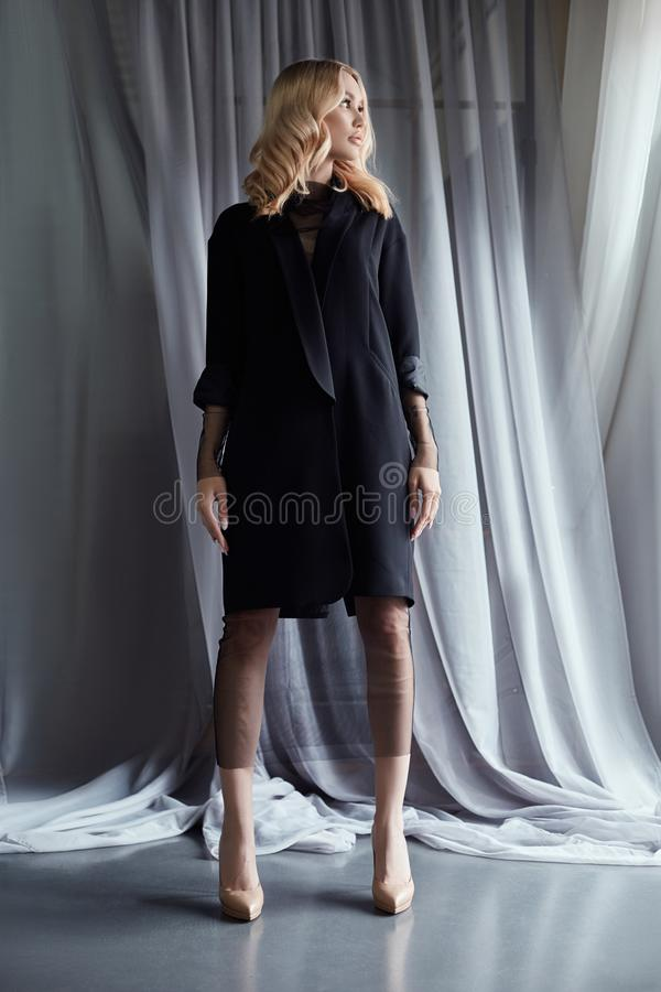 Blonde woman in a black autumn coat stands near a large window. Autumn fashion clothes, beautiful curly hair and a perfect figure stock photography
