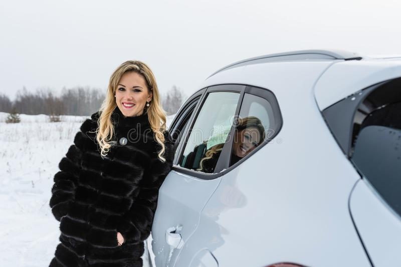 The blonde woman in a black fur coat stands at a white car and smilling royalty free stock photography