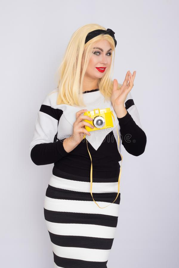 Caucasian blonde woman making shoot with yellow camera stock photo