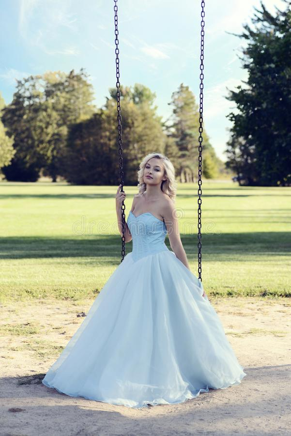 Blonde woman in blue dress playing on swing royalty free stock image