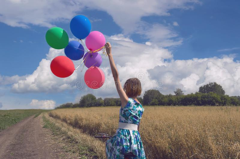 Blonde woman in blue floral dress riding a bicycle and holding balloons royalty free stock photos