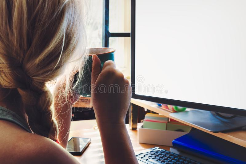 Blonde woman with braided hair sitting in front blank PC screen. Holding hot cup of coffee in her hands royalty free stock photos