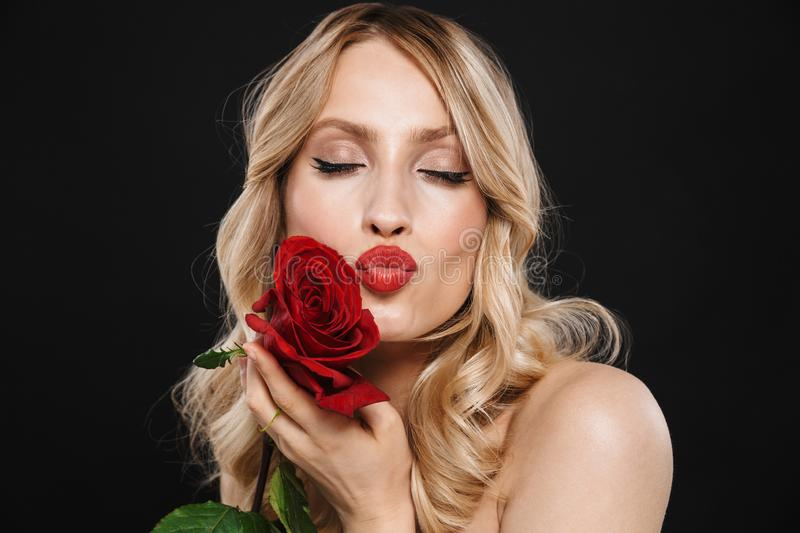 Blonde woman with bright makeup red lips posing isolated over black wall background holding rose flower stock photos