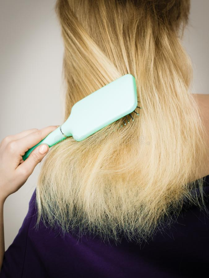 Blonde woman brushing hair back view royalty free stock photography