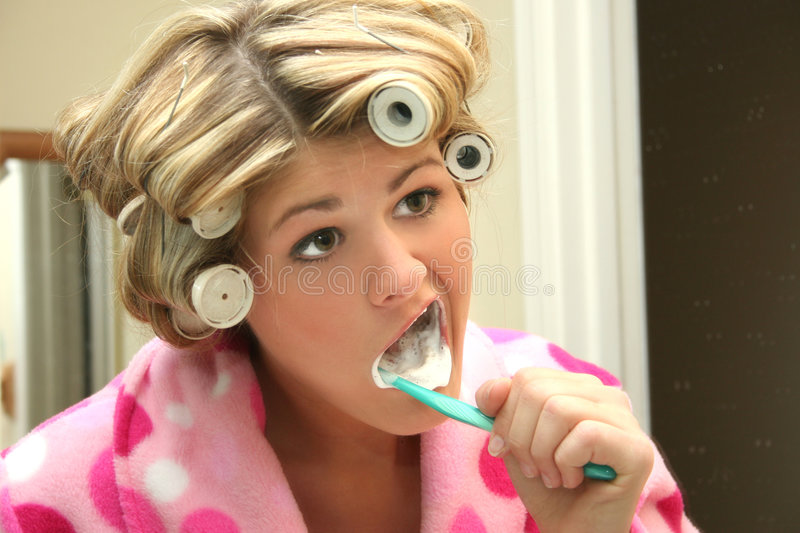 Blonde Woman Brushing Teeth. Beautiful blonde woman brushing teeth in bath robe and hair rollers. Shot with a Canon 20D stock images