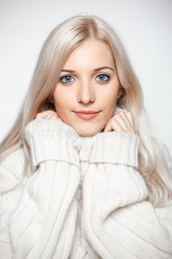 Blonde woman in cashmere sweater. Blonde young beautiful woman dressed in large white cashmere sweater on gray background royalty free stock image