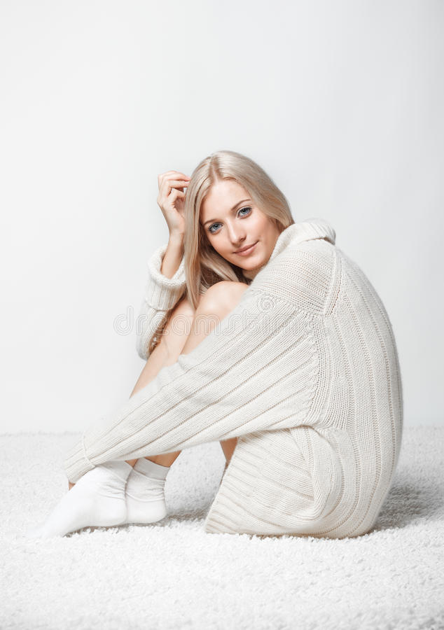 Blonde woman in cashmere sweater. Blonde young woman dressed in long white cashmere sweater sitting on white whole-floor carpet and gray background royalty free stock photos