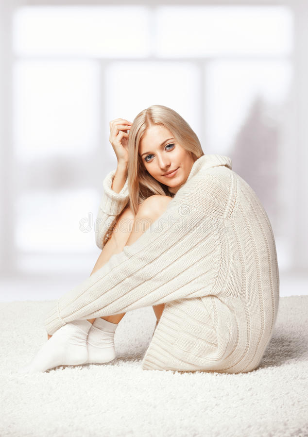 Blonde woman in cashmere sweater. Blonde young woman dressed in long white cashmere sweater sitting on white whole-floor carpet and window background stock photos