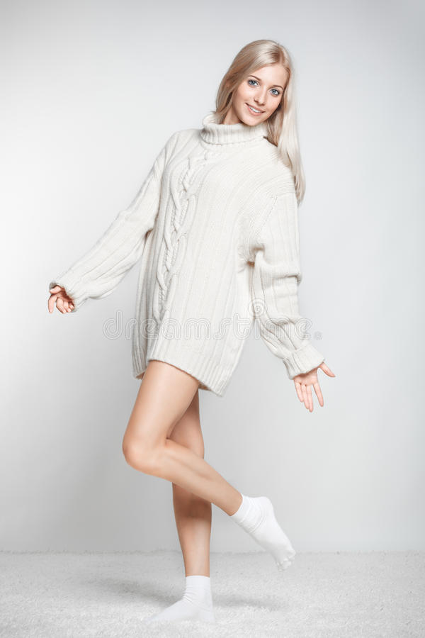 Blonde woman in cashmere sweater. Blonde young woman dressed in long white cashmere sweater on white whole-floor carpet and gray background royalty free stock image