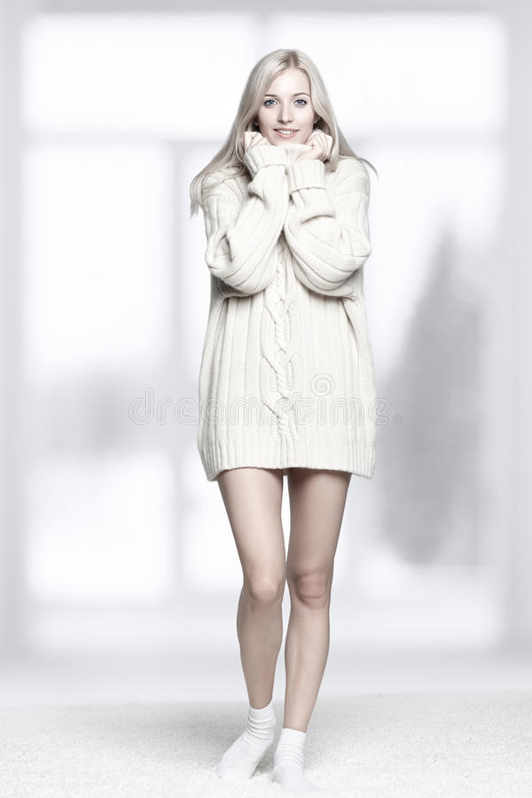 Blonde woman in cashmere sweater. Blonde young woman dressed in long white cashmere sweater on white whole-floor carpet and window background stock photo