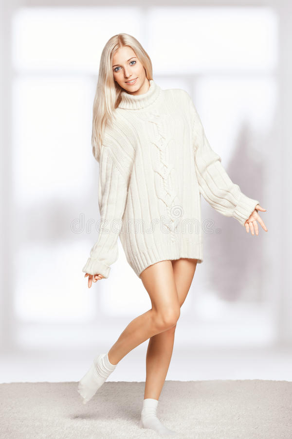 Blonde woman in cashmere sweater. Blonde young woman dressed in long white cashmere sweater on white whole-floor carpet and window background stock photography