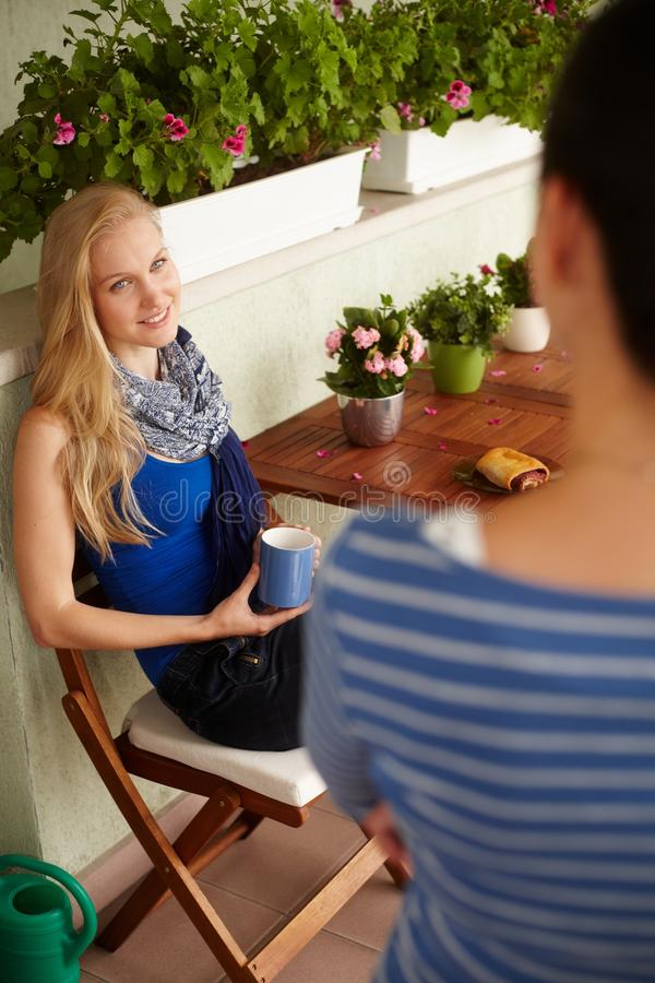 Blonde woman chatting with friend. Young blonde women chatting with female friend at balcony, drinking tea royalty free stock image