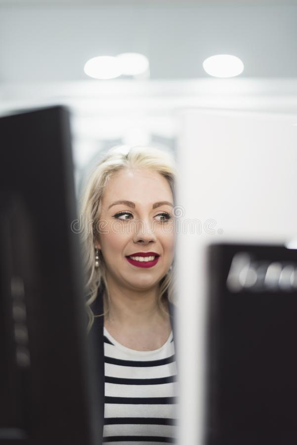 Blonde woman at commputer in workplace smiling stock photo