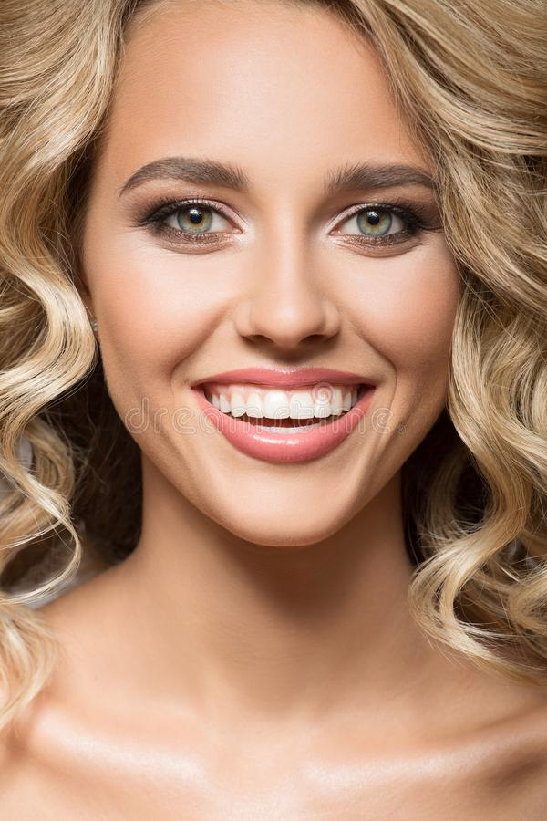 Blonde woman with curly beautiful hair smiling. Close up portrait royalty free stock image