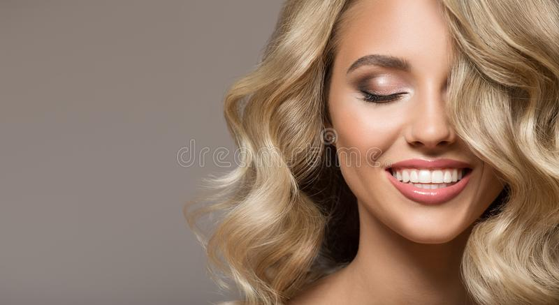 Blonde woman with curly beautiful hair smiling. On gray background royalty free stock photo