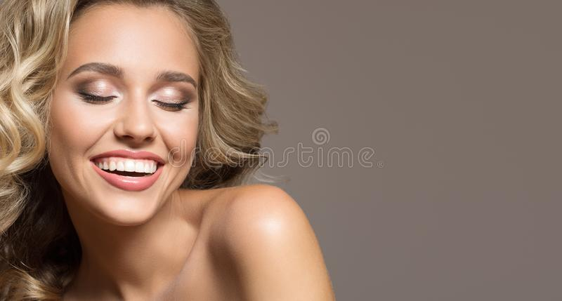 Blonde woman with curly beautiful hair smiling. On gray background royalty free stock image