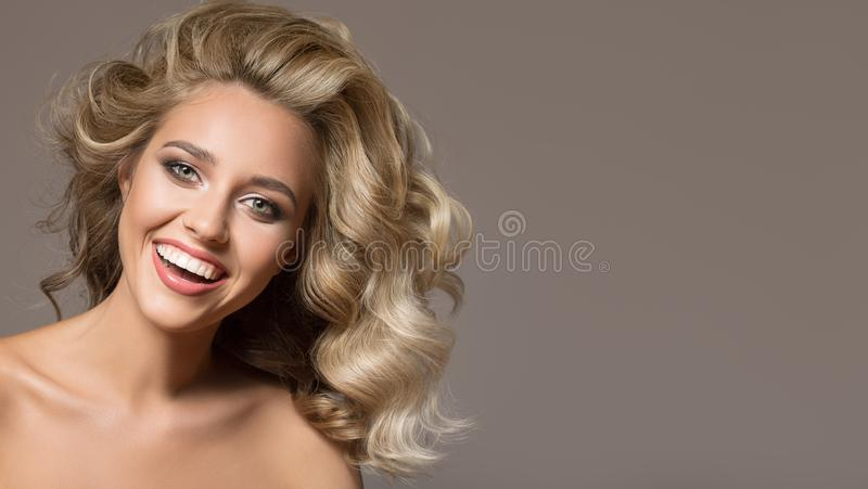 Blonde woman with curly beautiful hair smiling. On gray background stock photos